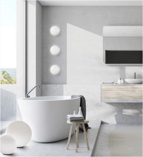 A modern bathroom, with a vessel tub and globe-shaped floor lamps